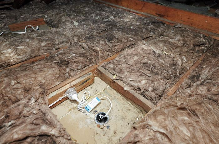Insulation in a roof space with a gap around a light fitting