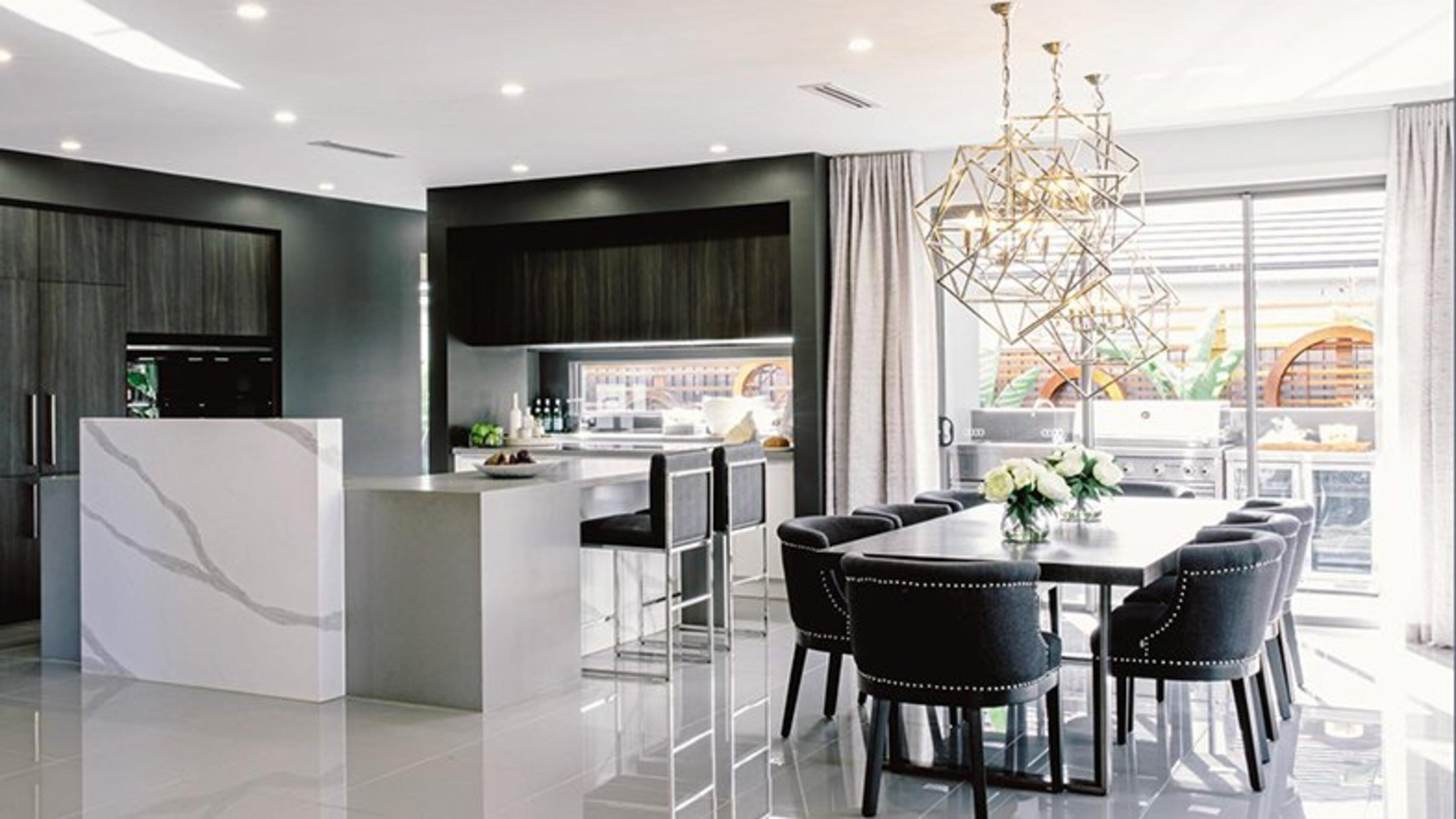 A kitchen with cool tones and a dining area with a table and pendant lighting.