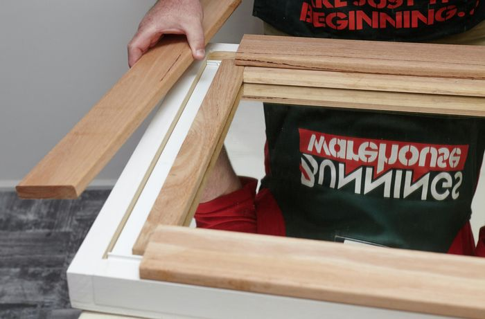 A person assembling lengths of timber into a rectangular frame for a mirror