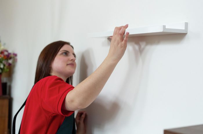 Person fitting a shelf onto mounts in a wall