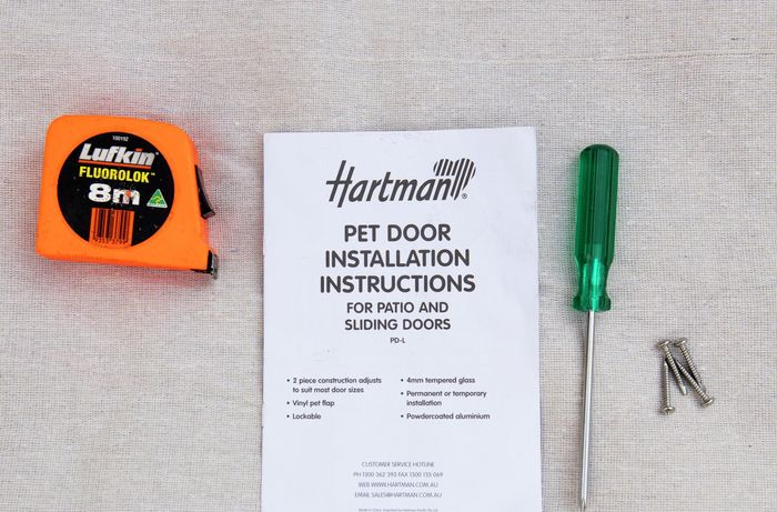Measuring tape, pet door installation instruction booklet and screwdriver on table top.