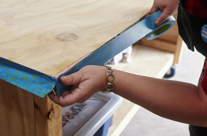 A person sticking masking tape to the edge of a plywood benchtop