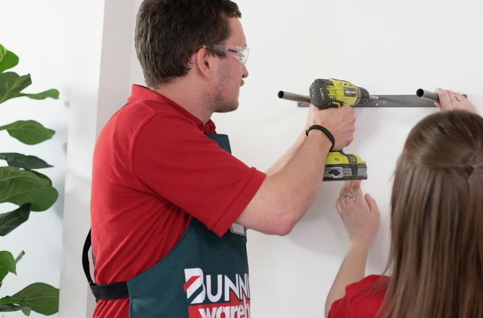Bunnings team members mounting floating shelf supports