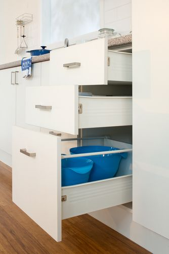 Three kitchen drawers holding bowls and other utensils
