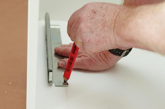 Person marking inside of drawer with pencil.