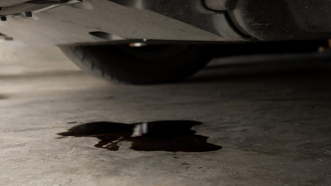 A patch of oil underneath a car on a driveway