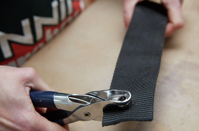 A person using a crimping tool to crimp eyelets in a length of webbing