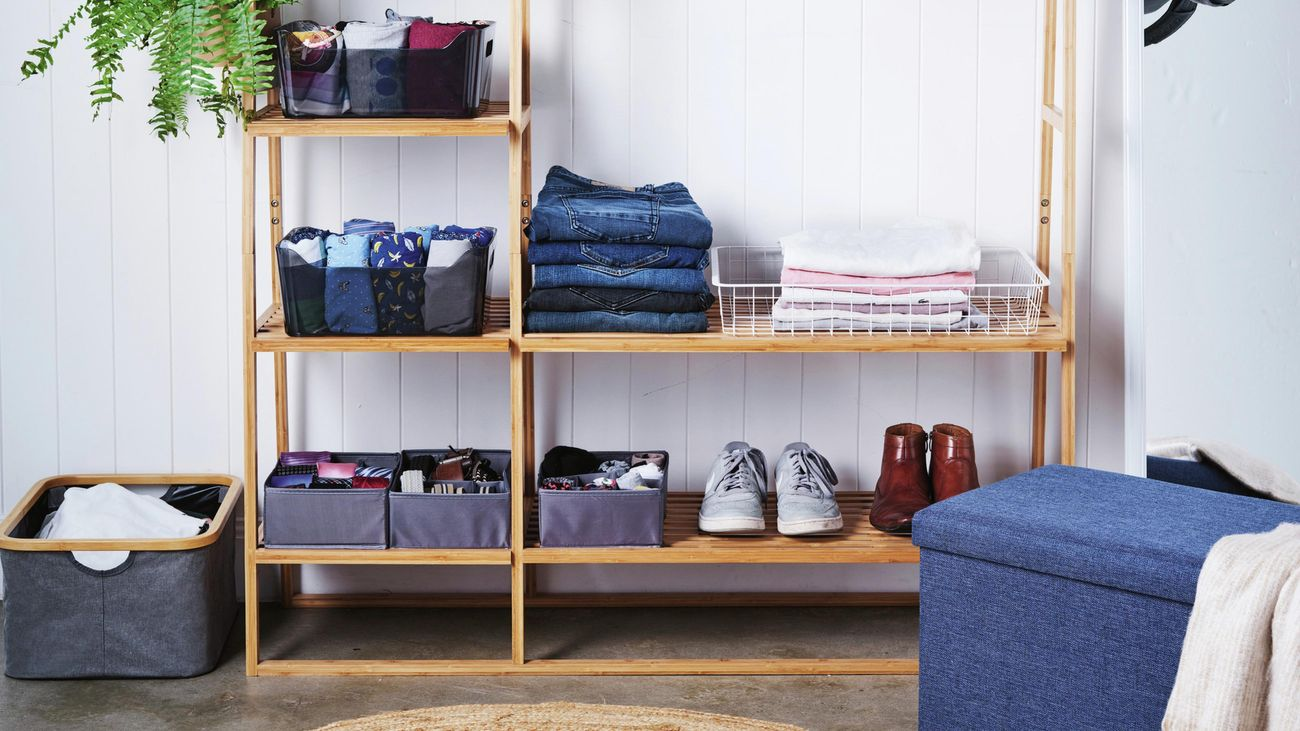 Organised bedroom timber clothing rack, with fabric organisers housing folded clothing, accessories and hanging bags on hooks with shoes on bottom rack.