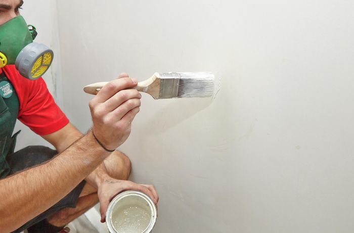 A person painting a patched area in a plaster wall