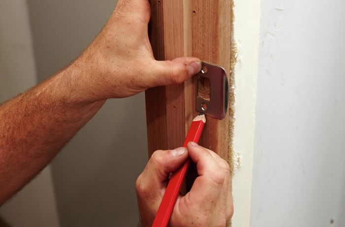 An outline being drawn around a door latch onto a door frame for later drilling
