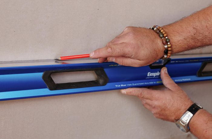 A spirit level being used to mark a straight line on a wall