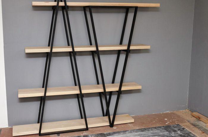 DIY industrial wooden bookshelf against a grey wall.
