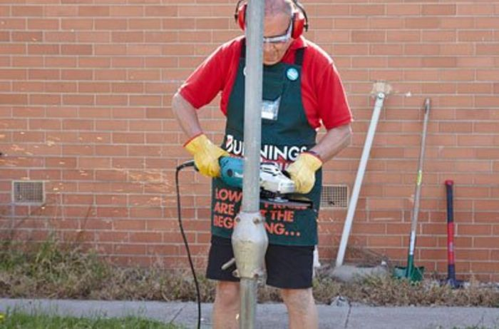 A Bunnings team member cutting through the rotary clothesline pole with an angle grinder.