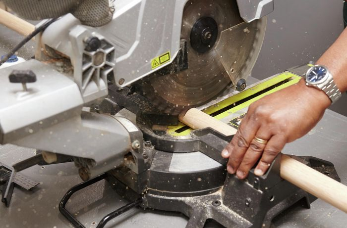 A mitre saw cutting a bar stool leg from a length of dowel