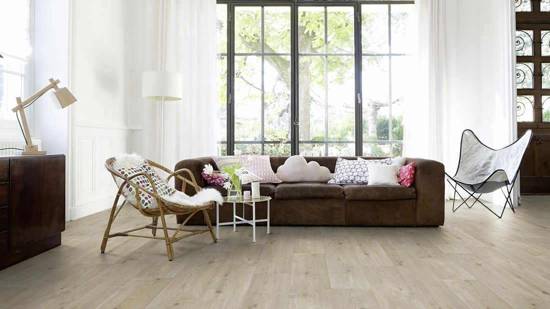 Living room with timber flooring and brown couch.