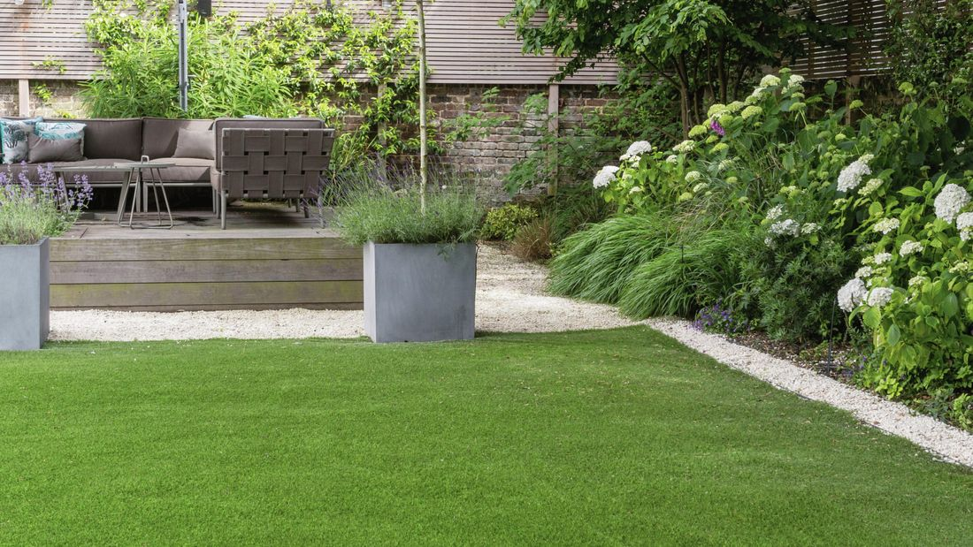 A garden with lush green grass and raised entertaining area