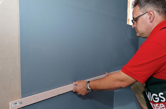 Person holding temporary shelf against wall.