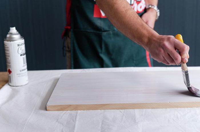 Bunnings team member painting the timber with a paint brush