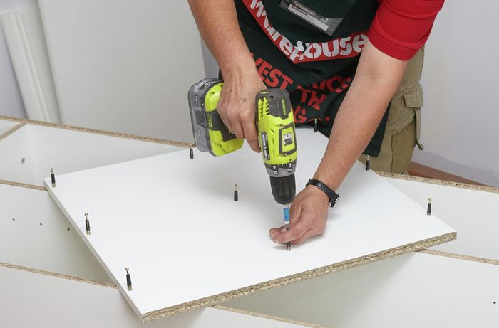 Person drilling into a panel.