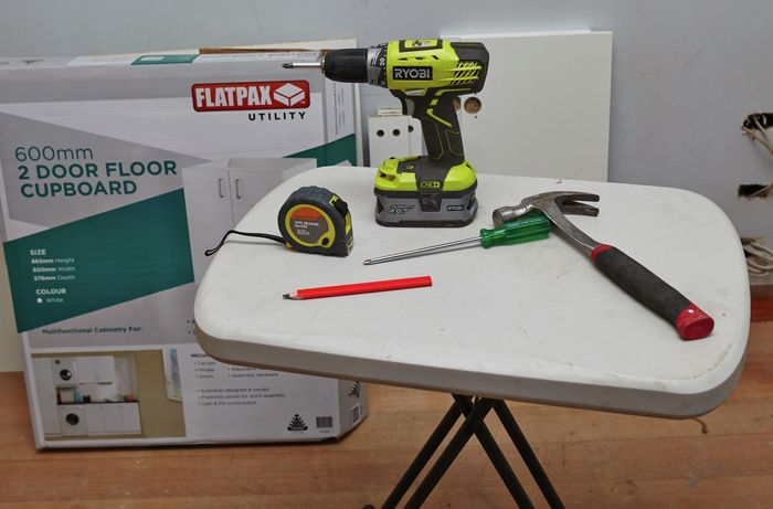 A tape measure, drill, hammer, screwdriver and pencil on a table