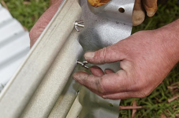 Person tightening nuts and bolts to hold corrugated iron garden bed together.
