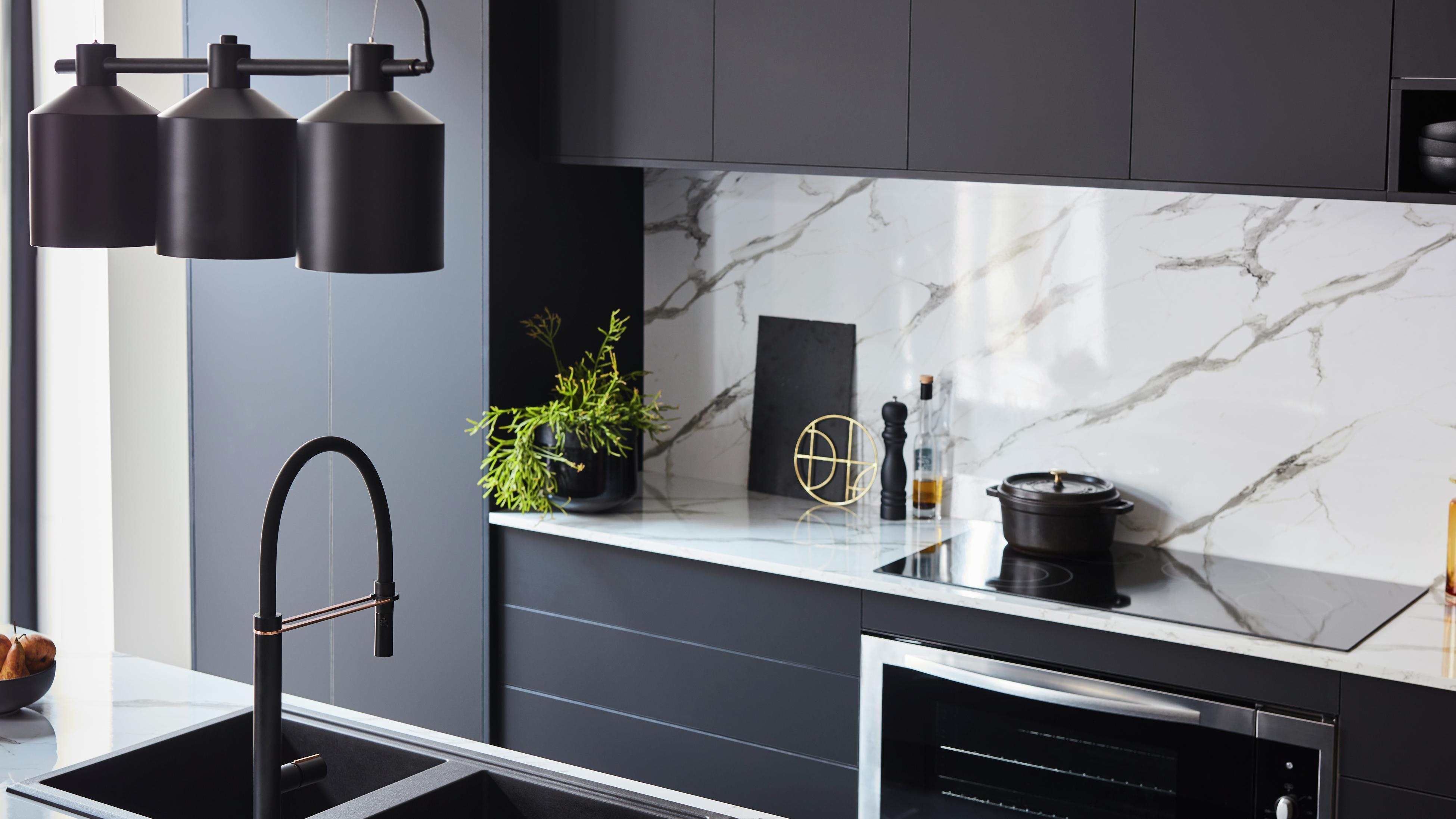 Monochromatic kitchen featuring marble splashback and black sink.