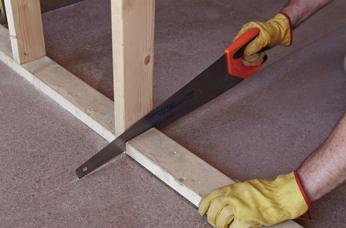 Person sawing stud wall frame.