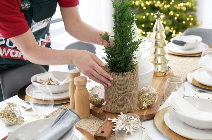 Person placing a miniature conifer tree on a table set with decorations