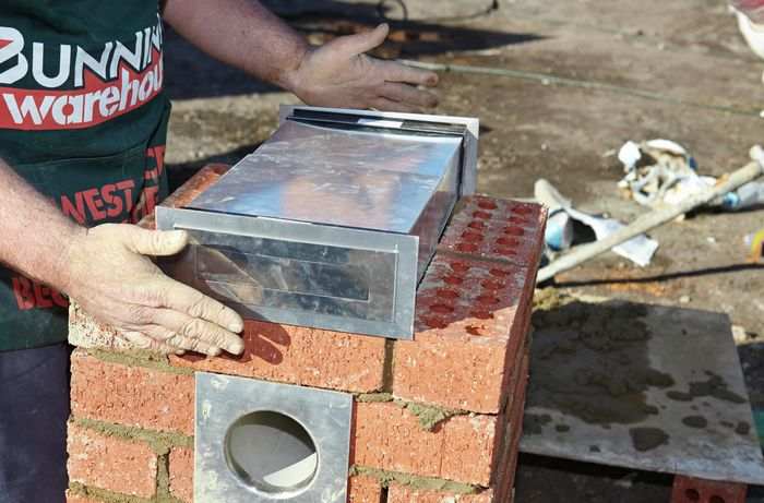 A steel mail slot being added to a middle layer of a brick letterbox