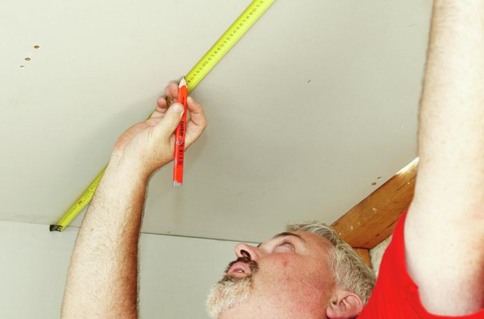 A Bunnings team member marking out the position of a skylight onto the ceiling with a tape measure and pencil