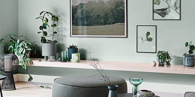 Living room with plants, green wall and bench seat.