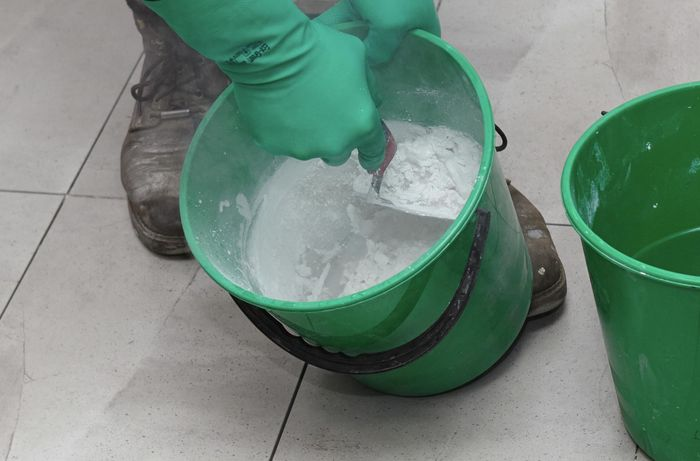 Grout being mixed in a bucket with a trowel