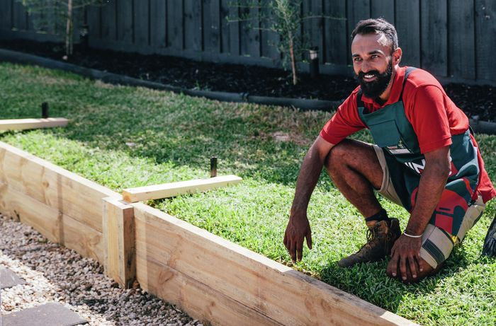 A Bunnings team member with a finished retainer wall