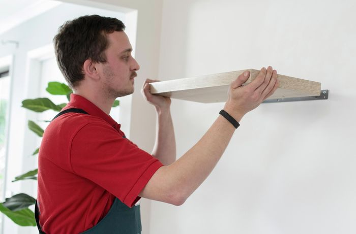 A floating shelf being positioned on wall mounted supports