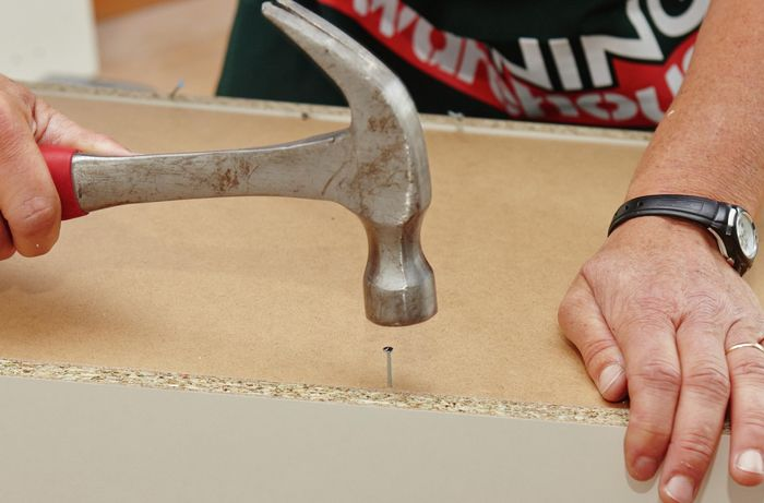 Hammering on a nail on the back panel