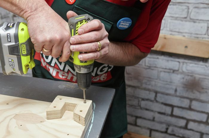Person drilling holes into timber bracket.