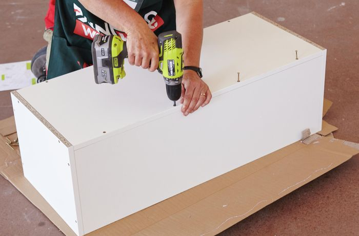 Person attaching panels to cabinet