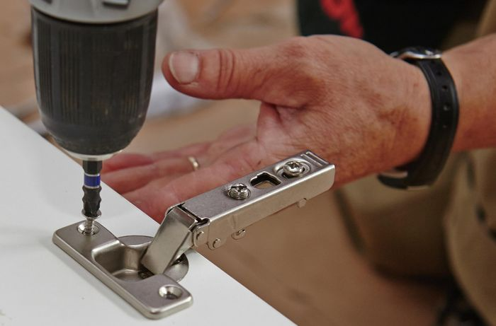 Screwing in a hinge into the pre-drilled holes