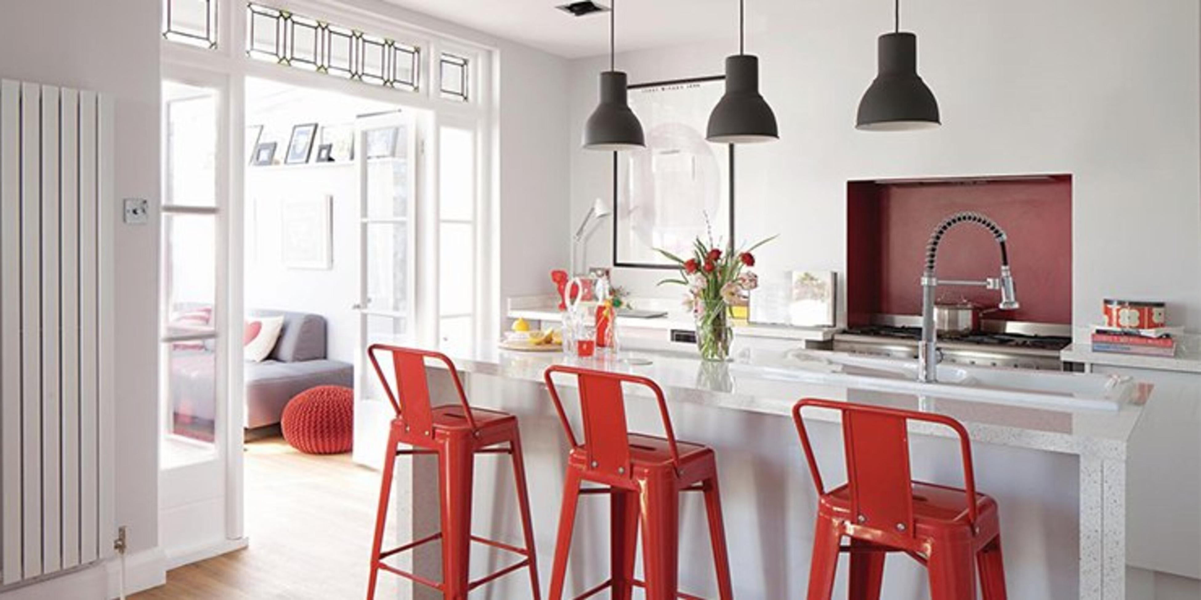 Kitchen with marble kitchen island and benchtops and red stools