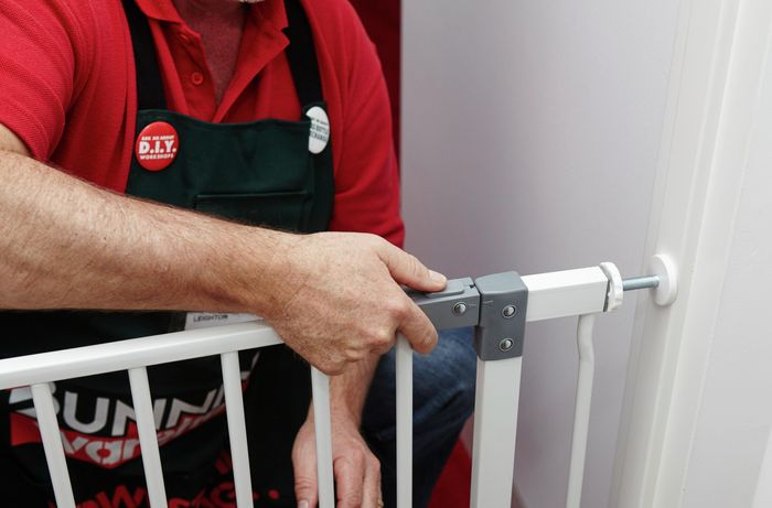 A person fitting a child security gate