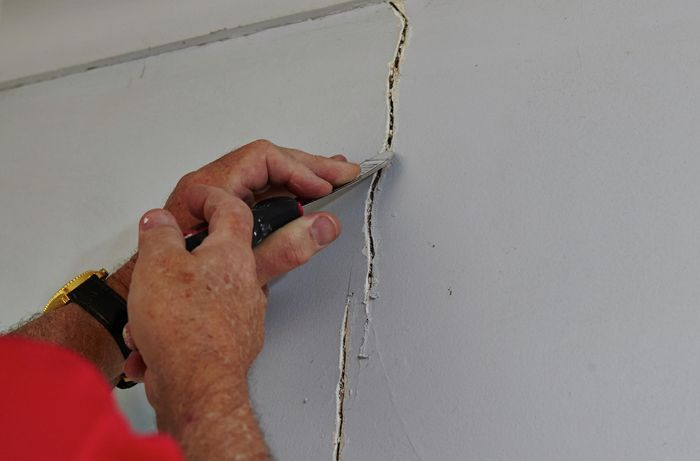 Person scraping crack with putty knife.