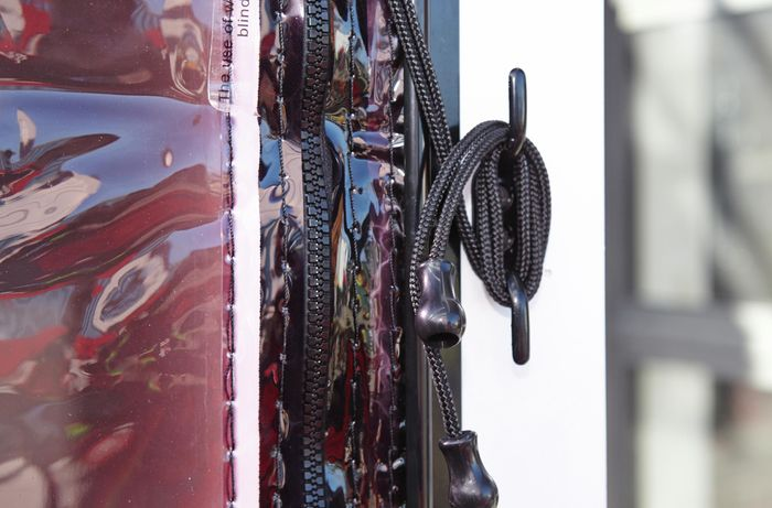 A close-up of a blind cord wrapped around a cleat on a post