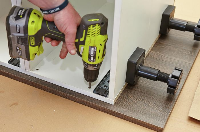 A person attaching cabinets to side panel using a cordless driver
