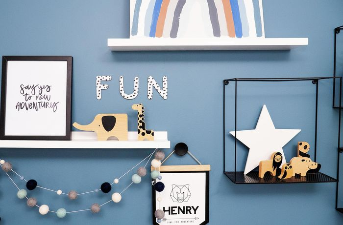 Blue wall with floating shelves and animal decorations.