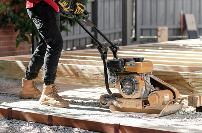 Person using a compactor on a gravel base.