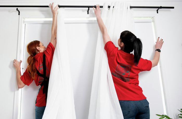 Two people putting up curtain rod with sheer white curtains on it.
