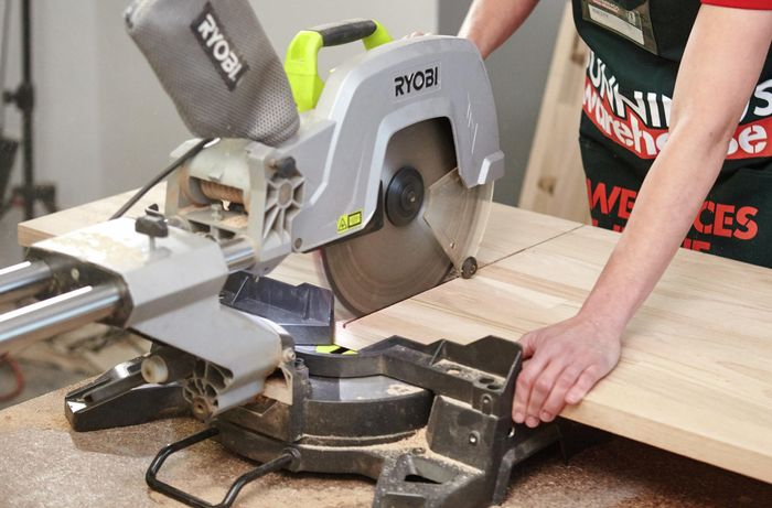 A person cutting a timber panel using a drop saw