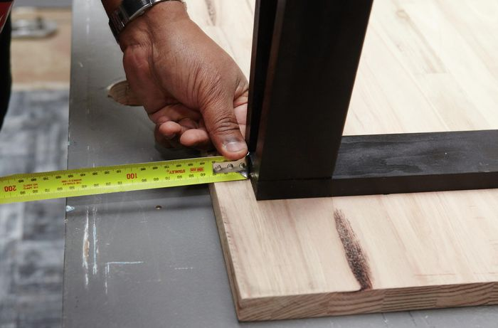 A person measuring distance from the edge of table top on an inverted table