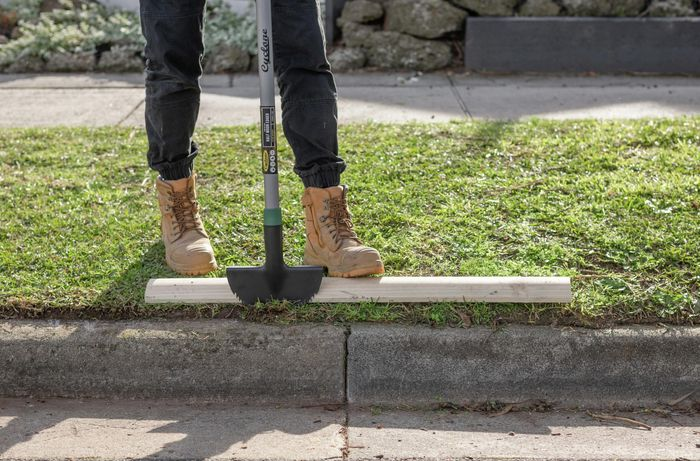 Person trimming lawn edges with trimming tool and piece of timber.