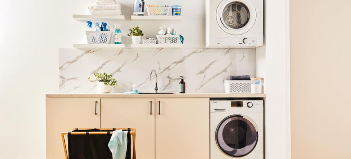organised laundry with a washing machine and cabinets